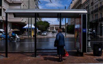 κυρία περιμένει σε στάση λεωφορείου